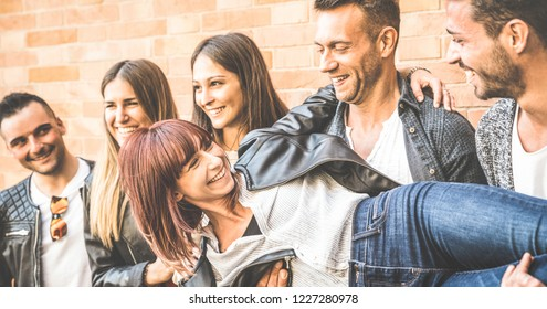 Multicultural guys and girls millennial holding female friend and having genuine fun at brick stone wall in the city - Urban youth concept with young people sharing time outdoors - Warm vintage filter