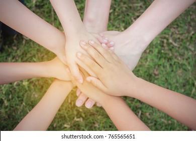 Multicultural hands, children hands on grass background. Hands toghether. Support, teamwork, togetherness concept