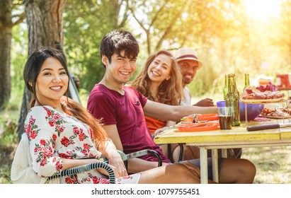 Multicultural happy friends eating and drinking beers at barbecue dinner at sunset - Young people having meal together outdoor - Focus on asian girl - Summer lifestyle, party and friendship concept