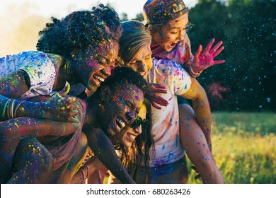 multicultural happy friends piggybacking together at holi festival