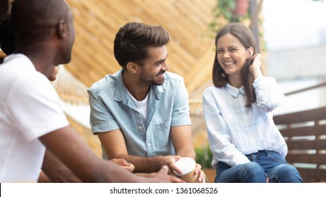 Multicultural happy people laughing at funny joke talking at reunion meeting on cafe terrace outdoor, cheerful diverse friends having fun drink coffee enjoy laughter, multi-ethnic friendship hangout