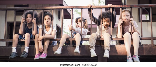 Multicultural little children sitting behind the fence. Homeless orphan stressful kids, education human right day concept banner