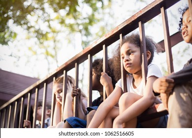 Multicultural little children sitting behind the fence. Homeless orphan stressful kids, education human right day concept