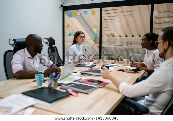 Multicultural male and female financial experts collaborating togetherness during brainstorming process in conference room of company,financial professionals planning strategy during meeting in office