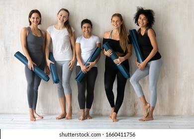 Multicultural millennial students girls holding mats resting after work out posing smiling looking at camera, activewear fashion store advertisement, sport club studio gym instructors portrait concept