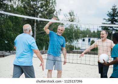 multicultural old friends playing volleyball on beach on summer day