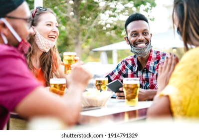 Multicultural people drinking beer with open face masks - New normal gathering concept with friends having fun together on happy hour at brewery bar - Bright filter with focus on afroamerican guy - Shutterstock ID 1914791329