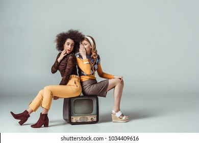 multicultural retro styled girls gossiping and sitting on vintage television