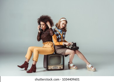 multicultural retro styled girls sitting on old tv and talking by stationary telephone