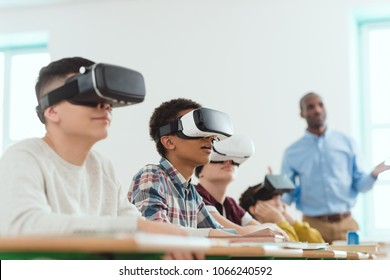 Multicultural schoolchildren using virtual reality headsets and african american teacher standing behind
