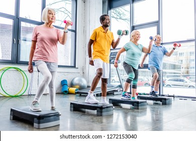 multicultural senior sportspeople synchronous exercising with dumbbells on step platforms at gym