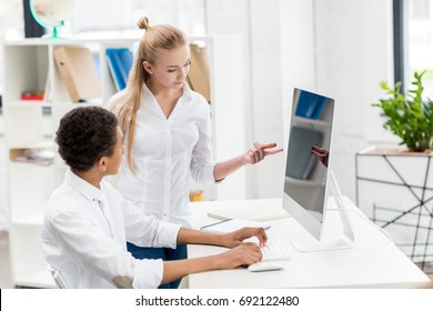 multicultural students discussing task at computer screen in class