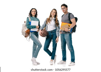 multicultural students looking at camera with books and basketball ball isolated on white
