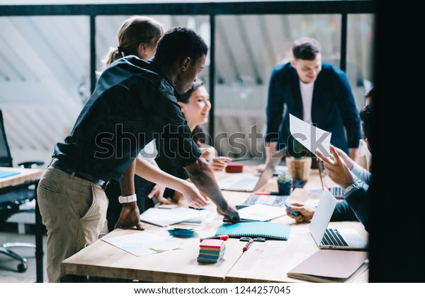 Multicultural team group of creative young people discussing business startup project at meeting table during brainstorming in modern office. Collaborative process of designers with productivity
