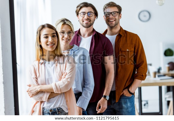 multicultural team of startup project standing and looking at camera in office