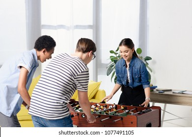 multicultural teenagers playing table football at home