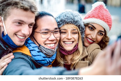 Multicultural travelers taking happy selfie wearing face mask and winter clothes - New normal lifestyle concept with milenial friend having fun together outside - Vivid filter with focus on blond girl