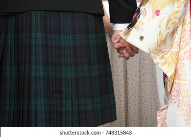 A multicultural wedding, with a Scottish groom wearing a kilt, and a Japanese bride in a wedding kimono, holding hands.