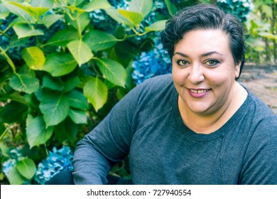 multicultural woman sitting in garden smiling