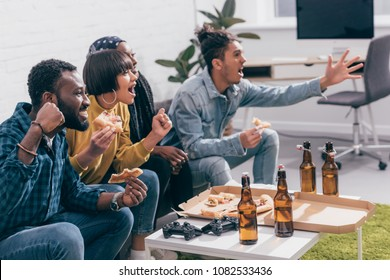 multicultural young friends sitting on couch near table with pizza and beer bottles while watching american football match