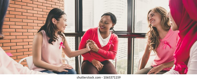 Multiethinic women wearing pink color clothes sitting in circle talking and meeting for breast cancer awareness campaign, panoramic banner