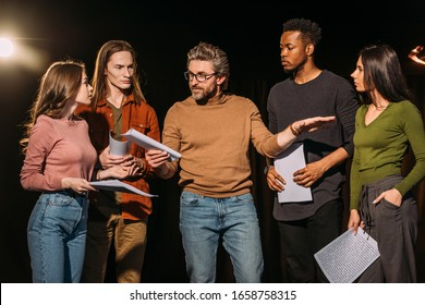 multiethnic actors and actresses rehearsing with theater director on stage