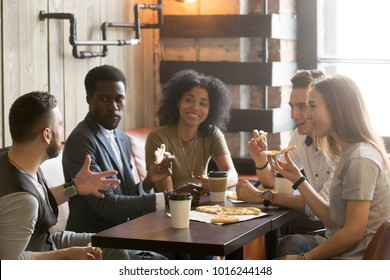 Multi-ethnic african and caucasian friends talking eating pizza in pizzeria, diverse young people enjoy italian food at meeting, multiracial students having conversation during lunch together in cafe