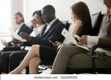 Multi-ethnic applicants sitting in queue preparing for interview, black and white vacancy candidates waiting on chairs holding resume using smartphones, human resources, hiring and job search concept