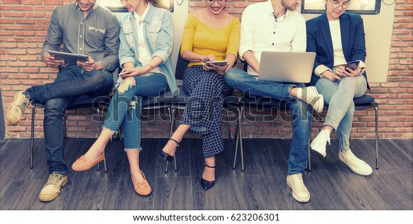 Grupo multiétnico asiático de negocios con traje informal usando smartphone, tablet y laptop para trabajar o jugar a redes sociales y sitio web en oficina moderna. Concepto de negocio y tecnología