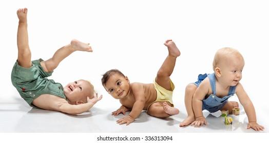 Multiethnic babies dancing on light background