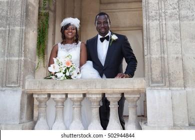 Multi-ethnic bride and groom hugging outdoor,
