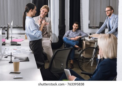 multiethnic business colleagues having conversation after work in office