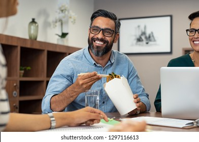 Multiethnic business man with colleagues having chinese take away food. Friendly businessman and casual businesswoman eating noodles. Mature latin man eating lunch meal while talking to creative team.