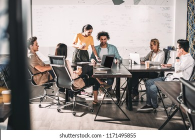 multiethnic business partners having meeting at table with laptops in modern office
