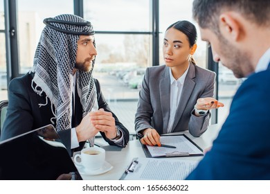 multiethnic business partners on meeting with translator in office