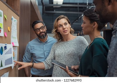 Multiethnic business people discussing charts and graphs showing the results of their successful teamwork. Mature business woman showing presentation to casual colleagues in during night meeting.