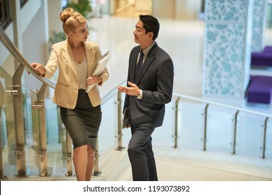 Multi-ethnic business people walking up the stairs and discussing work