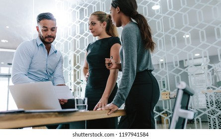 Multi-ethnic business professionals discussing over a document boardroom. Business colleagues working on their new business plan together at office.