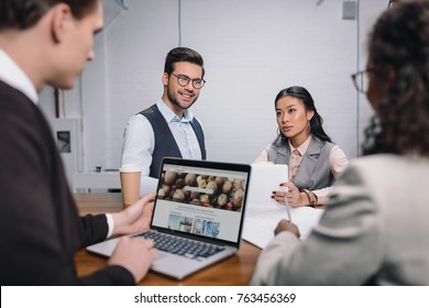 multiethnic business team with documents and laptop with depositphotos website