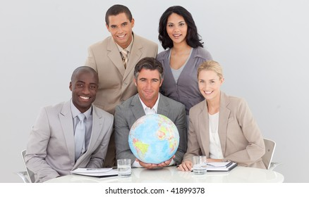 Multi-ethnic business team holding a terrestrial globe in the office