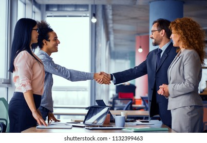 Multiethnic business teams at meeting room shaking hands. Handshake of two men. Toned concept.