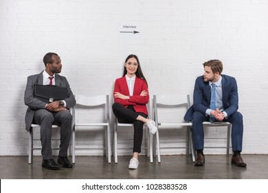 multiethnic businessmen looking at smiling asian businesswoman while waiting for job interview