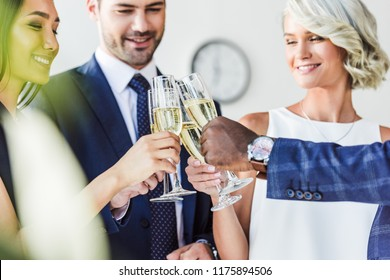 multiethnic businesspeople clinking with glasses of champagne in office