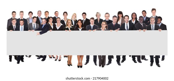 Multiethnic businesspeople holding blank billboard against white background