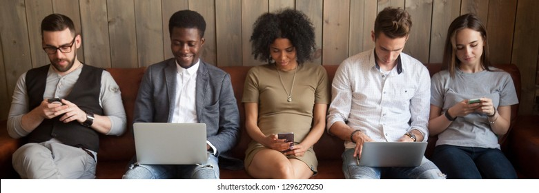 Multi-ethnic businesspeople sitting in row on couch absorbed in mobile phones computers girls guys addicted in gadgets devices. Overuse dependence on internet concept, banner for website header design