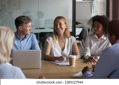 Multi-ethnic businesswomen and businessmen gathered together at business meeting in contemporary conference room, all attention of associates is focused on millennial attractive coach or team leader