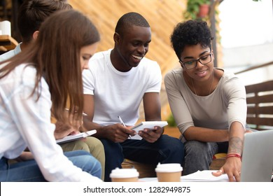 Multi-ethnic cheerful friends girls and guys preparing for university exam together, students sitting outdoors holding notepads writing notes and ideas using computer for e-learning studying online