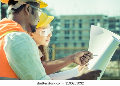 multi-ethnic civil engineers or construction worker foreman looking at project blueprint at the construction site
