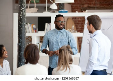 Multiethnic colleagues talk making flipchart presentation to coworkers during meeting, African American coach present project interacting with employees, diverse workers brainstorm at training