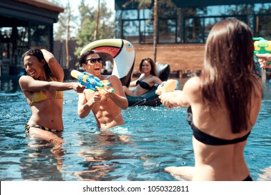 Multiethnic company of friends in swimming pool at summertime. Swimming pool party. Group of people are having fun in swimming pool at summertime.